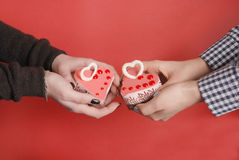 Female hands keep heart-shape cake with candle. Royalty Free Stock Images