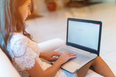 Female hands on keyboard with opened web page in browser at screen. Cropped image of woman surfing the internet her Royalty Free Stock Photography