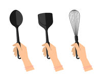 Female hands with kitchen utensils: spoon, spatula and whisk. Stock Photography