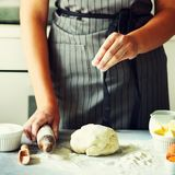 Female hands kneading dough, baking background. Cooking ingredients - eggs, flour, sugar, butter, milk, rolling pin on stock photo
