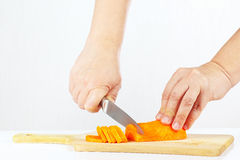 Female hands with a knife chops carrot on a wooden cutting board Royalty Free Stock Photos
