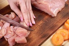 Female hands with a knife, cuts the meat on the wooden board . Healthy eating and lifestyle. Female hands with a knife, cuts the meat on the wooden board royalty free stock images