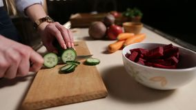 Female hands with knife cutting cucumber on board stock footage