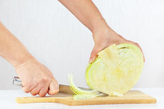 Female hands with a knife shred cabbage Stock Photos