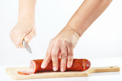 Female hands with a knife sliced salami on a cutting board Royalty Free Stock Images