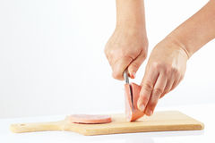 Female hands with a knife sliced sausage on a wooden cutting board Stock Photo