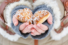 Female hands in knitted grey mittens hold beautiful heart shaped Stock Image