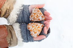 Female hands in knitted grey mittens hold beautiful heart shaped. Biscuit cookies with white icing at snow background. Focus on cookies. Top view stock photos