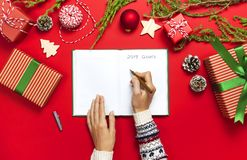 Female hands in knitted sweater are writing with pen in clean notebook plans for the new year, gift boxes, fir branches on red bac. Kground flat lay Christmas royalty free stock photo