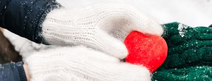 Female hands in knitted white mittens with heart of snow in winter day. royalty free stock photography