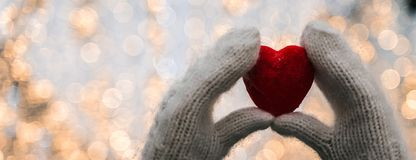 Female hands in knitted white mittens with heart of snow in winter day. Love and St. Valentine cozy concept, copyspace, bokeh background, banner stock images