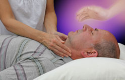 Receiving spiritual help during a healing session. Female hands laid either side of a male patient`s throat channeling energy, together with the help of a higher Royalty Free Stock Images