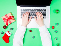Female hands with laptop and Christmas gifts Stock Images