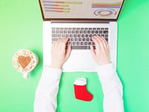 Female hands and laptop with Christmas sock Royalty Free Stock Photo