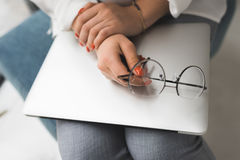 Female hands with laptop and eyeglasses in office Stock Image