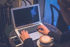 Female hands on laptop keyboard in coffee shop royalty free stock images