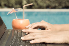 Female hands on laptop keyboard at the poolside royalty free stock photo