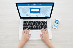Female hands in laptop and phone with social network on the scre Stock Images