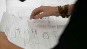 Female hands lay out sketches of clothes. Drawn on paper
