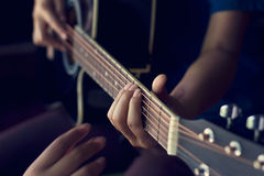 Female hands learning to play on acoustic guitar Royalty Free Stock Photo