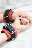Female hands in leather handcuffs. on the. Background sheet. sex toys. passion stock image