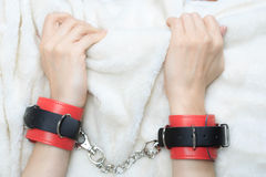 Female hands in leather handcuffs. eagerly grabbed. The sheets.. sex toys. passion royalty free stock image