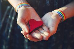 Female hands with LGBT colorful rainbow ribbon wristbands holding red wooden heart. Same sex marriage, gay and lesbian couple and relationship concept royalty free stock images