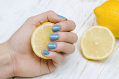 Female hands with light blue nail art holding lemon. Royalty Free Stock Image