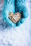 Female hands in light teal knitted mittens with entwined beige flaxen heart on a white snow background. St. Valentines Day concept