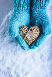 Female hands in light teal knitted mittens with entwined beige flaxen heart on a white snow background. St. Valentines Day concept. Female hands in light teal Stock Photography