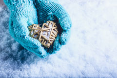 Female hands in light teal knitted mittens with entwined beige flaxen heart on a white snow background. St. Valentines Day concept. Female hands in light teal Stock Photo