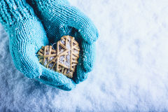 Female hands in light teal knitted mittens with entwined beige flaxen heart on a white snow background. St. Valentines Day concept. Female hands in light teal Royalty Free Stock Photos