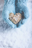 Female hands in light teal knitted mittens with entwined beige flaxen heart on a white snow. Love, St. Valentines Day concept. Female hands in light teal knitted Royalty Free Stock Images