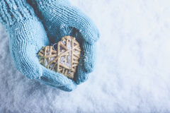 Female hands in light teal knitted mittens with entwined beige flaxen heart on a white snow. Love, St. Valentines Day concept. Female hands in light teal knitted Stock Photo