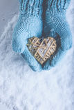 Female hands in light teal knitted mittens with entwined beige flaxen heart on a white snow. Love, St. Valentines Day concept Stock Image