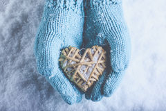 Female hands in light teal knitted mittens with entwined beige flaxen heart on a white snow. Love, St. Valentines Day concept. Female hands in light teal knitted Royalty Free Stock Photo