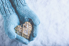 Female hands in light teal knitted mittens with entwined beige flaxen heart on a white snow. Love, St. Valentines Day concept
