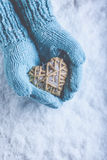 Female hands in light teal knitted mittens with entwined beige flaxen heart on a white snow. Love, St. Valentines Day concept. Female hands in light teal knitted Stock Photos