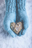Female hands in light teal knitted mittens with entwined beige flaxen heart on a white snow. Love, St. Valentines Day concept. Female hands in light teal knitted Stock Image