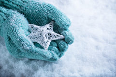 Female hands in light teal knitted mittens with entwined white star on a white snow background. Winter and Christmas concept stock image