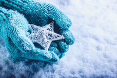 Female hands in light teal knitted mittens with entwined white star on a white snow background. Winter and Christmas concept. Stock Images