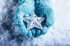 Female hands in light teal knitted mittens with entwined white star on a white snow background. Winter and Christmas concept. Stock Photo