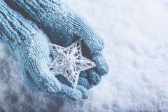 Female hands in light teal knitted mittens with entwined white star on a white snow background. Winter and Christmas concept. Royalty Free Stock Photos