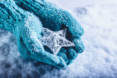 Female hands in light teal knitted mittens with entwined white star on a white snow background. Winter and Christmas concept. Stock Photos