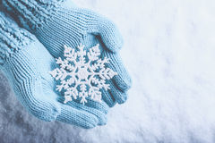 Female hands in light teal knitted mittens with sparkling wonderful snowflake on snow background. Winter and Christmas concept Stock Photography