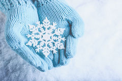 Female hands in light teal knitted mittens with sparkling wonderful snowflake on snow background. Winter and Christmas concept Stock Photo