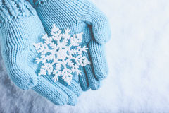 Female hands in light teal knitted mittens with sparkling wonderful snowflake on snow background. Winter and Christmas concept