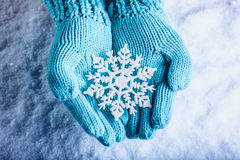 Female hands in light teal knitted mittens with sparkling wonderful snowflake on a white snow background. Winter Christmas concept Royalty Free Stock Photos