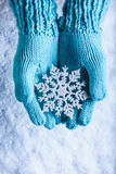 Female hands in light teal knitted mittens with sparkling wonderful snowflake on a white snow background. Winter Christmas concept Royalty Free Stock Photo