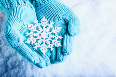 Female hands in light teal knitted mittens with sparkling wonderful snowflake on a white snow background. Winter Christmas concept Stock Photos